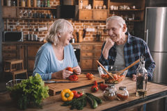Senior couple cooking together and smiling each other stock photo