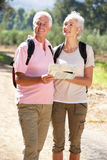Senior couple on country walk reading map Royalty Free Stock Images