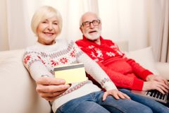 Senior couple with credit card. Happy senior couple with credit card and laptop shopping online royalty free stock photos