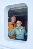 Senior couple on cruise ship. Smiling, attractive senior couple on cruise ship, looking out of the stateroom (cabin) window royalty free stock photos