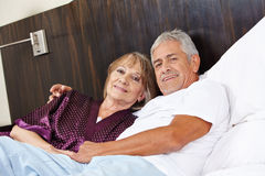 Senior couple cuddle in bed. Senior couple in love cuddle in a hotel bed stock photography