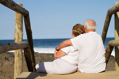 Senior couple cuddling. Rear view of senior couple cuddling on beach Stock Images