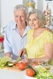 Senior couple cutting vegetable. Happy senior couple cutting vegetables for salad Stock Photography