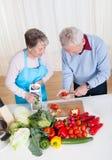 Senior couple cutting vegetables Stock Photos