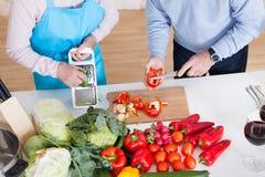 Senior couple cutting vegetables Stock Photo