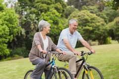 Senior couple on cycle ride in countryside. Side view of a senior couple on cycle ride in countryside Stock Images