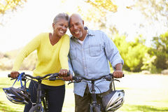 Senior Couple On Cycle Ride In Countryside. Smiling To Camera Royalty Free Stock Photos