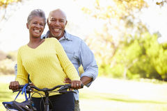 Senior Couple On Cycle Ride In Countryside. Smiling To Camera Stock Photo