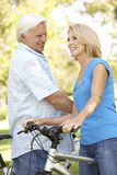 Senior Couple On Cycle Ride In Park Stock Photo