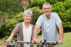 Senior couple on cycle ride at park Royalty Free Stock Photos