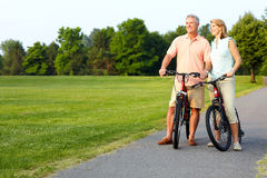 Senior couple cycling. Happy elderly senior couple cycling in park