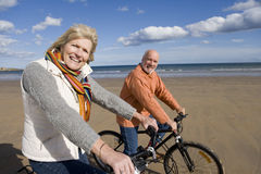 Senior couple cycling on beach, smiling, portrait, side view royalty free stock photos