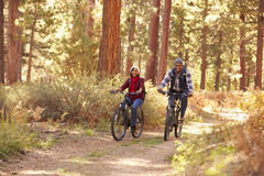Senior Couple Cycling Through Fall Woodland Royalty Free Stock Photo