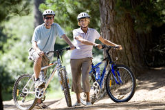 Senior couple, in cycling helmets, mountain biking on woodland trail, smiling, portrait Stock Image