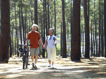 Senior couple in cycling helmets walking through wood with bicycles, holding hands, front view Stock Images