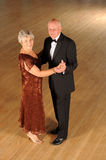 Senior couple in dance pose. Smiling senior citizen couple in semi-formal attire in a dance pose alone on a hardwood floor Royalty Free Stock Image