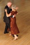 Senior couple dancing. Senior citizen couple in semi-formal attire dancing alone on a hardwood floor Stock Image