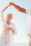 Senior couple dancing on the beach royalty free stock image