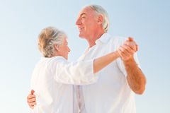Senior couple dancing on the beach Stock Photos