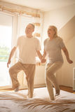 Senior couple dancing and jumping together on bed  holding hands Royalty Free Stock Images