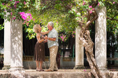 Senior couple dancing latin american dance for fun. Active retired people having fun, happy old men and women dancing latin american dance in patio stock photos
