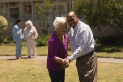 senior couple dancing together in garden royalty free stock image