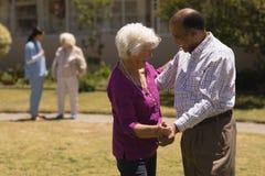 senior couple dancing together in garden stock photos