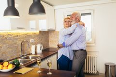 Senior couple dancing together in kitchen royalty free stock images
