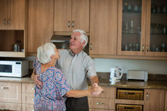 Senior couple dancing together in kitchen Stock Photo