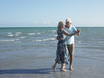 Senior Couple Dancing On Tropical Beach. Full length of happy senior couple dancing on tropical beach Royalty Free Stock Image