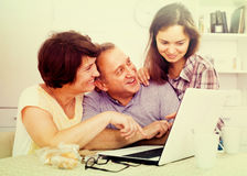 Senior couple and daughter with laptop at home Stock Image