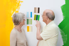 Senior couple deciding on a new paint colour. For their house looking at swatches on a wall on which they have already tested green and yellow paint Royalty Free Stock Photos