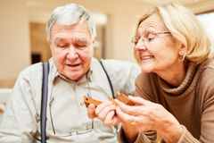 Senior couple plays with a wooden puzzle. Senior couple with dementia plays with a wooden puzzle as a therapy in the nursing home stock photos