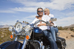 Senior couple on desert road sitting on motorcycle looking at camera Royalty Free Stock Photo