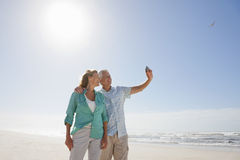 Senior couple with digital camera taking self-portrait on sunny beach Stock Images