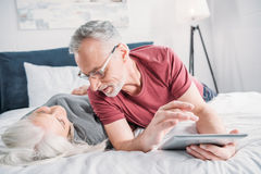 Senior couple with digital tablet resting in bed together Royalty Free Stock Images