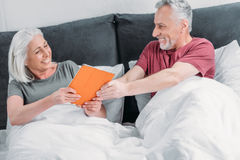 Senior couple with digital tablet resting in bed together Stock Photo