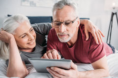 Senior couple with digital tablet resting in bed together Stock Photography