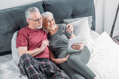 Senior couple with digital tablet resting in bed together Royalty Free Stock Photos