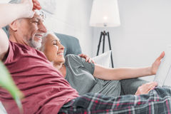 Senior couple with digital tablet resting in bed together royalty free stock image