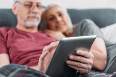 Senior couple with digital tablet resting in bed together Stock Images