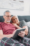 Senior couple with digital tablet resting in bed together royalty free stock photography