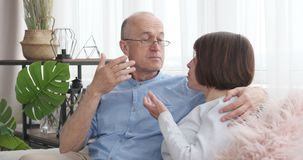 Senior couple discussing on sofa at home stock video footage