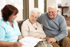 Senior Couple In Discussion With Health Visitor Stock Photo