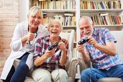 Senior couple and doctor playing video game stock images
