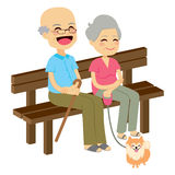 Senior Couple With Dog. Cute senior couple sitting on wooden bench with dog resting Royalty Free Stock Image