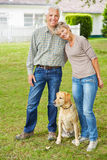 Senior couple with dog in front of house Royalty Free Stock Photography