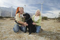 Senior Couple With Dog Near Wind Farm. Portrait of a happy Caucasian senior couple with dog near wind farm Royalty Free Stock Photography