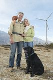Senior Couple With Dog Near Wind Farm. Portrait of a lovely Caucasian senior couple with dog near wind farm Royalty Free Stock Photos