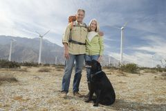 Senior Couple With Dog Near Wind Farm. Portrait of an active Caucasian senior couple with dog near wind farm Stock Photos